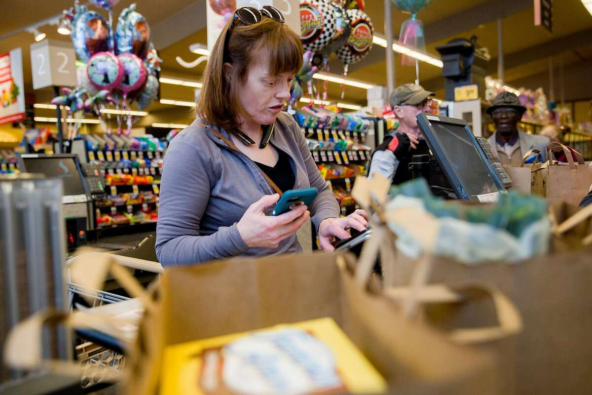 Grocery delivery shopper Courtney Fox of Newark purchases groceries for three separate Instacart orders at Safeway in Palo Alto, Calif. Tuesday, March 17, 2020. As a shopper for Instacart, Courtney Fox finds herself on the front lines of keeping homebound Bay Area people supplied with food and essentials during the threat of the Coronavirus and shelter-in-place order was given to six Bay Area counties on Monday, March 16.