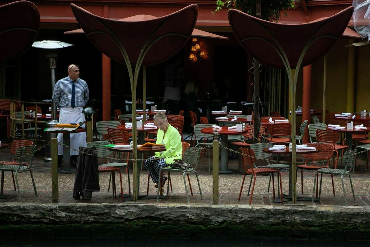 A woman has no trouble maintianing social distance while dining at a River Walk restaurant.