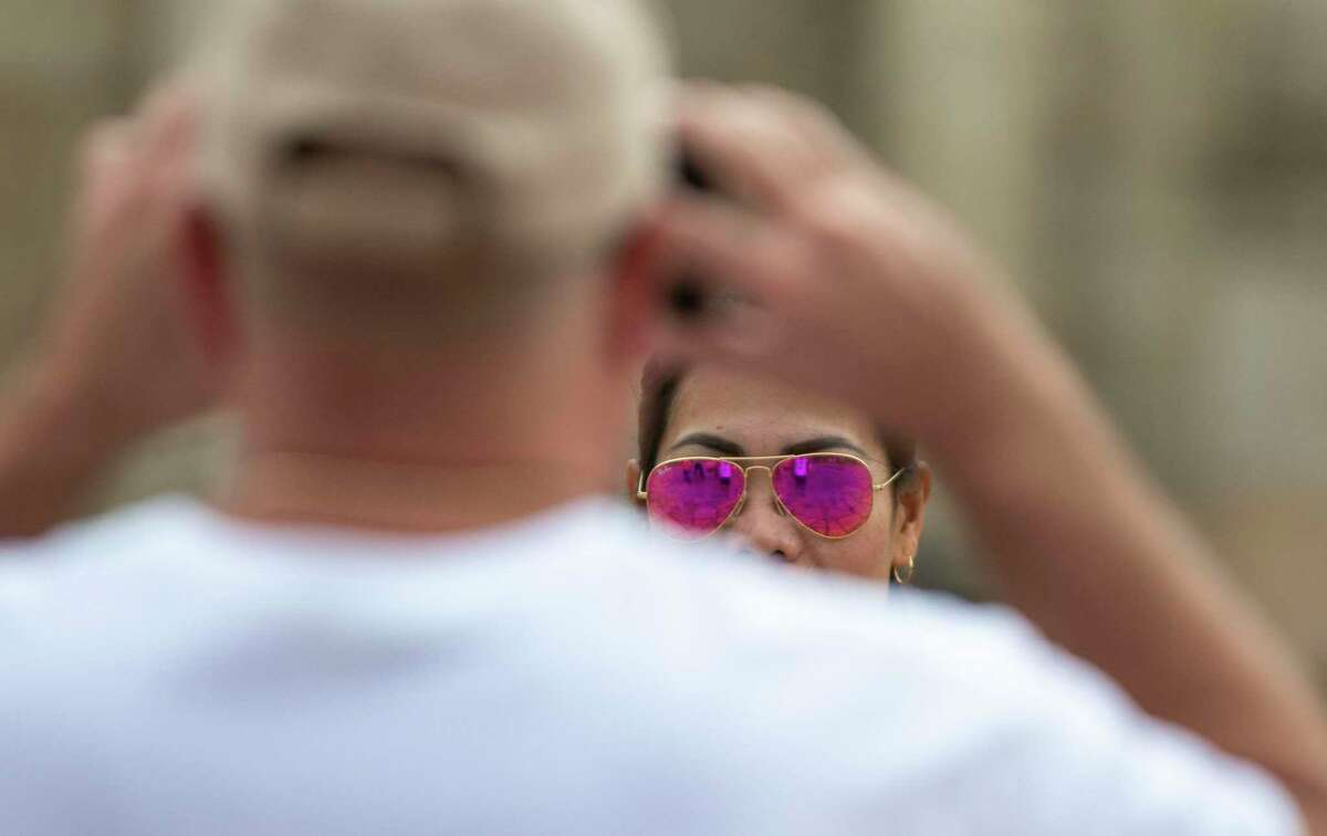 Ritchele Alota of the Philippines poses as Kyle Powell of Florida takes her picture in front of the Alamo in downtown San Antonio, Texas, on March 17, 2020.