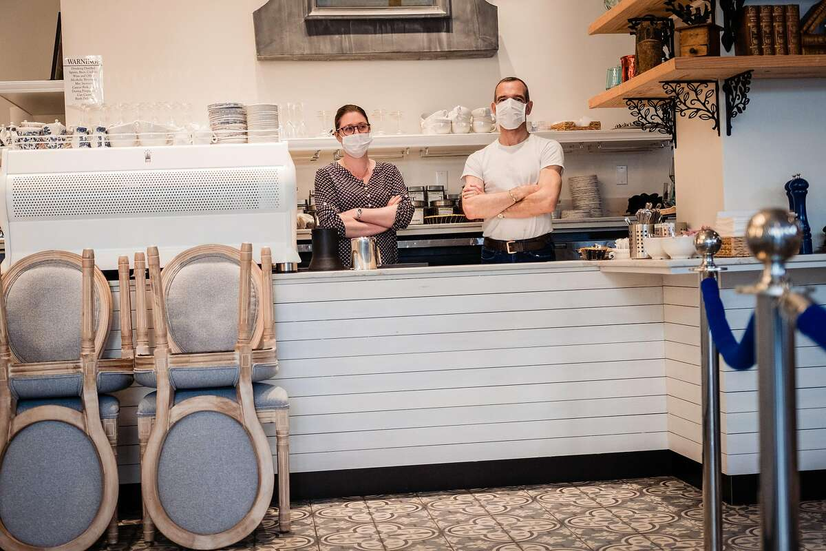 Danel De Betenlu and Magalie Chabot wait for take out orders behind the counter of Maison Danel a cafe on Polk Street that just opened two weeks in San Francisco, Calif. onTuesday, March 17, 2020.