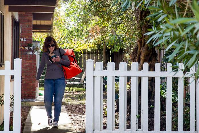 Grocery delivery shopper Courtney Fox of Newark delivers Instacart orders to various homes in Palo Alto, Calif. Tuesday, March 17, 2020. As a shopper for Instacart, Courtney Fox finds herself on the front lines of keeping homebound Bay Area people supplied with food and essentials during the threat of the Coronavirus and shelter-in-place order was given to six Bay Area counties on Monday, March 16.