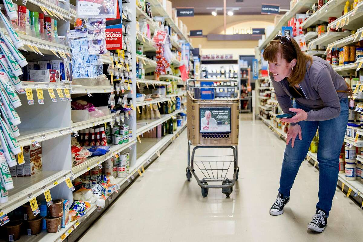 Grocery delivery shopper Courtney Fox of Newark searches for items for three separate Instacart orders at Safeway in Palo Alto, Calif. Tuesday, March 17, 2020. As a shopper for Instacart, Courtney Fox finds herself on the front lines of keeping homebound Bay Area people supplied with food and essentials during the threat of the Coronavirus and shelter-in-place order was given to six Bay Area counties on Monday, March 16.