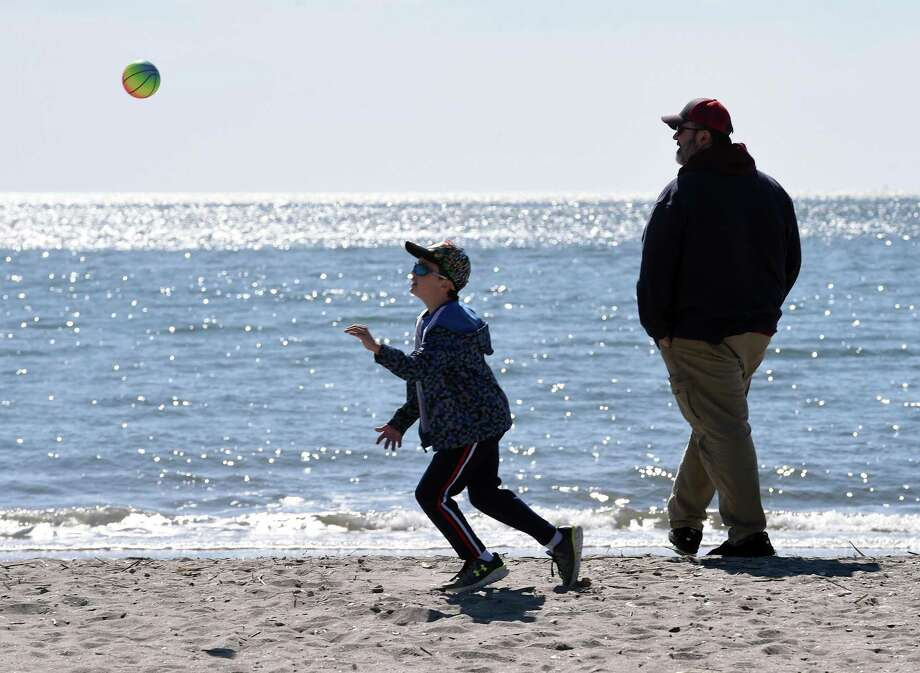 Logan McCormick (left), 7, of Enfield plays ball with his father, Mike, at Hammonasset Beach State Park's West Beach in Madison on March 15, 2020. Photo: Arnold Gold / Hearst Connecticut Media / New Haven Register