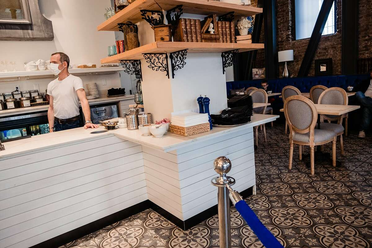 Danel De Betenlu owner of Maison Danel a cafe on Polk Street that just opened two weeks ago waits for take out orders behind the counter in San Francisco, Calif. onTuesday, March 17, 2020.