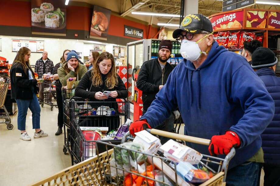 Mike Schwinn (right) and others wait on line at Safeway on 7th Avenue on Tuesday, March 17, 2020 in San Francisco, California. The city is on lockdown due to the coronavirus. Photo: Gabrielle Lurie, The Chronicle