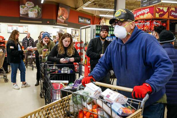 Mike Schwinn (right) and others wait on line at Safeway on 7th Avenue on Tuesday, March 17, 2020 in San Francisco, California. The city is on lockdown due to the coronavirus.