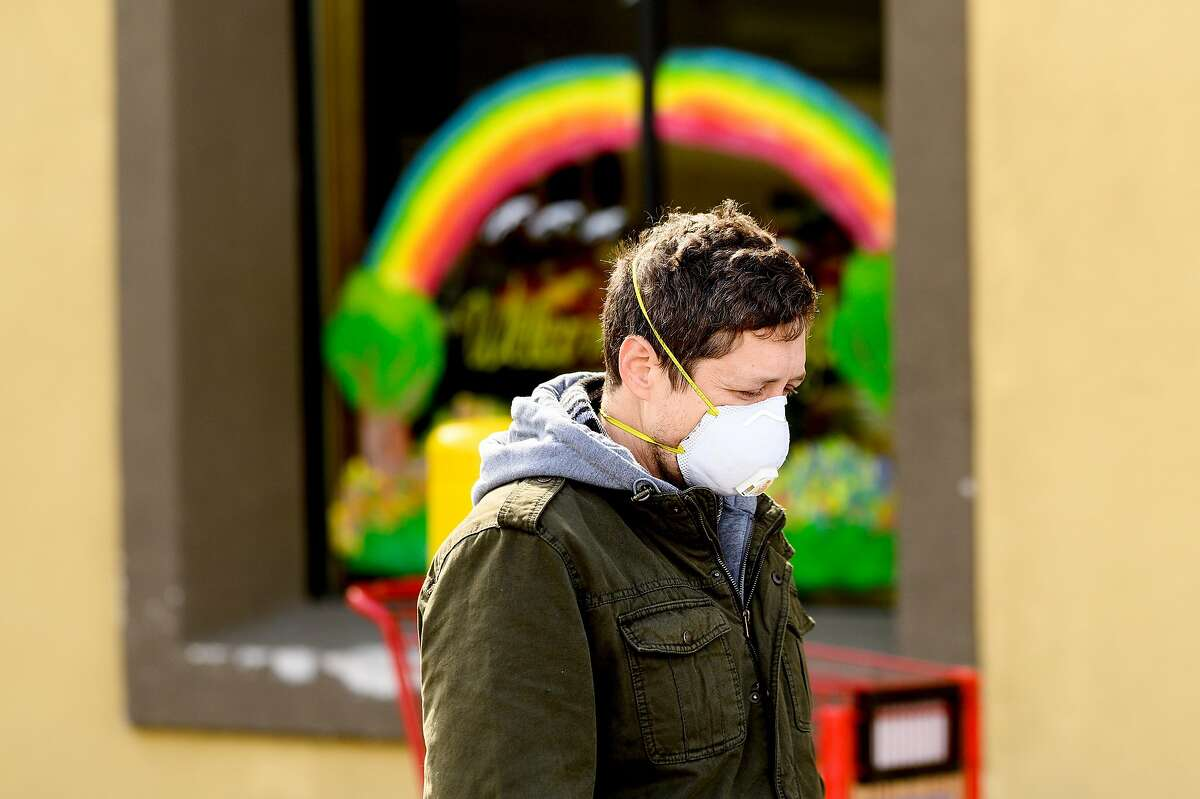 Nick Anderson wears a mask while waiting in line to shop at Trader Joe's in Oakland, Calif., on Tuesday, March 17, 2020, as Alameda County enters its first day of shelter in-place-orders to slow the spread of coronavirus.