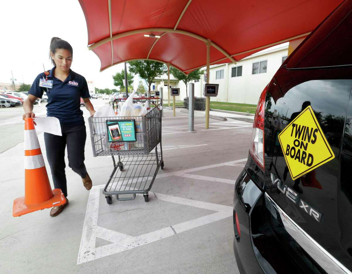 Nicole Cappelli, e store manager, pulls a cart of groceries to the car of customer, Monica Leal of Cypress, at the curbside grocery service at H-E-B, 9710 Katy Fwy., Tuesday, June 21, 2016, in Houston. With twin 20-month-old girls and a full-time job, Monica says it has been a lifesaver, giving her more flexibility in her own schedule since curbside service has removed the hassle from grocery shopping. ( Melissa Phillip / Houston Chronicle )