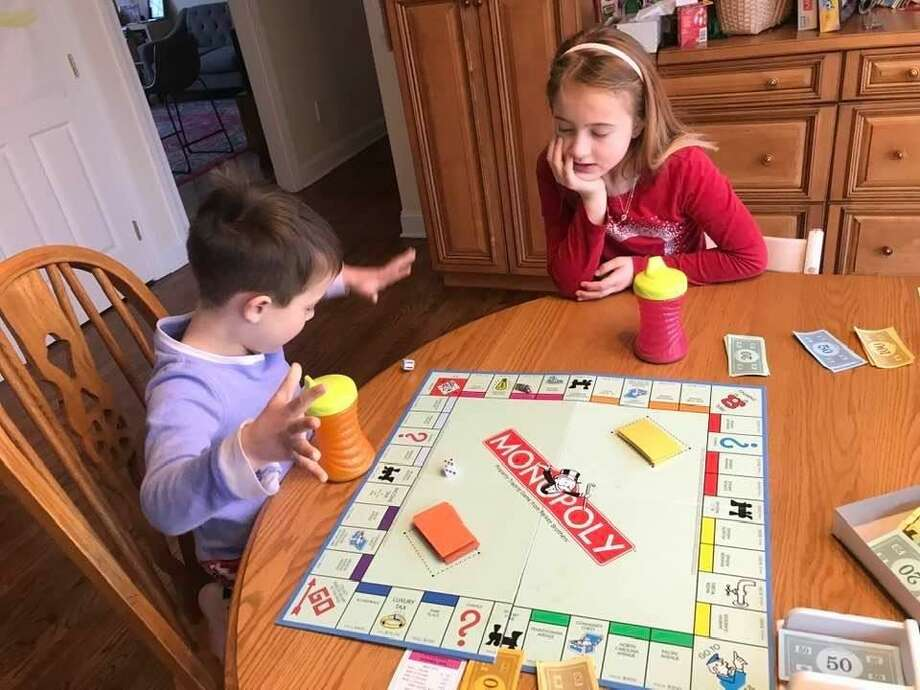 Spectrum/Families are finding creative ways to keep children engaged while learning and out of school. On Monday morning, Maggie and Geroge Hicks of New Milford practiced their math skills during a game of Monopoly. March 16, 2020 Photo: Courtesy Of Jeannette Reiling