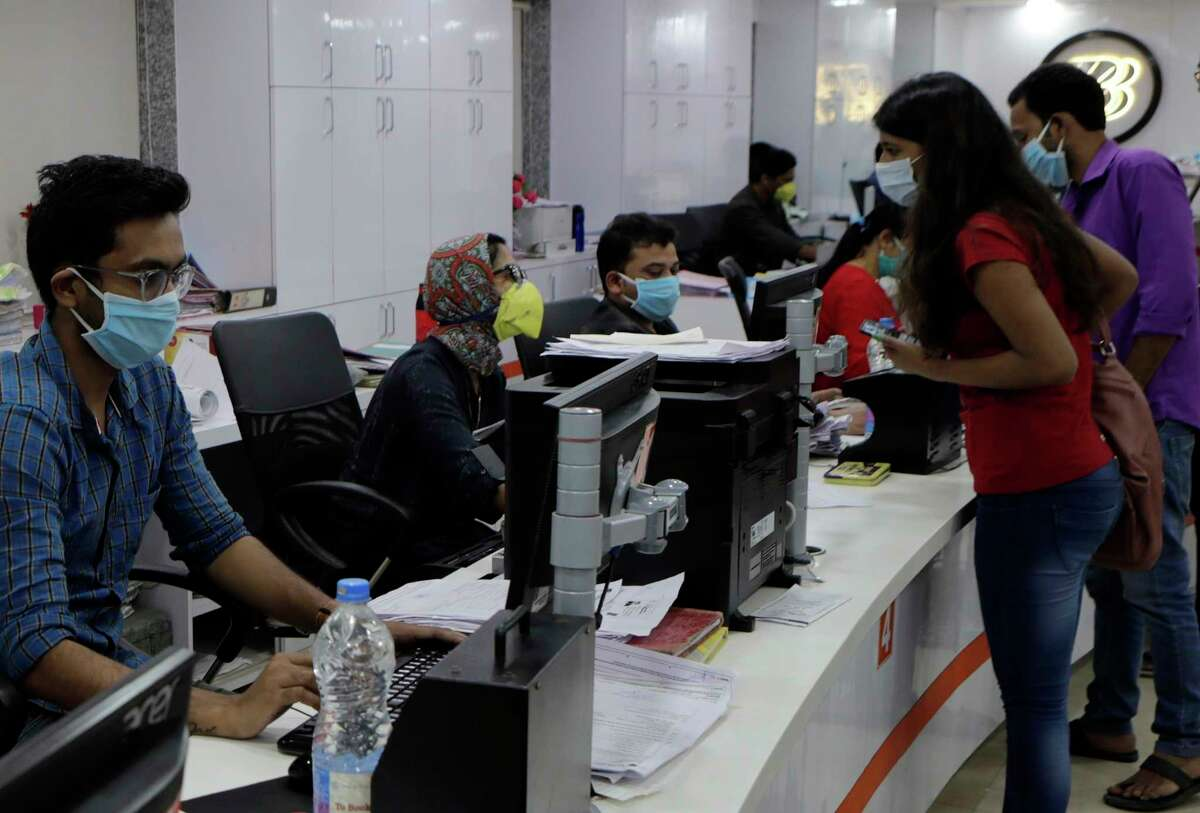 Indian bank employees and customers wear protective masks as a precaution against a new virus in Mumbai, India, Tuesday, March 17, 2020. For most people, the new coronavirus causes only mild or moderate symptoms. For some it can cause more severe illness. (AP Photo/Rajanish Kakade)