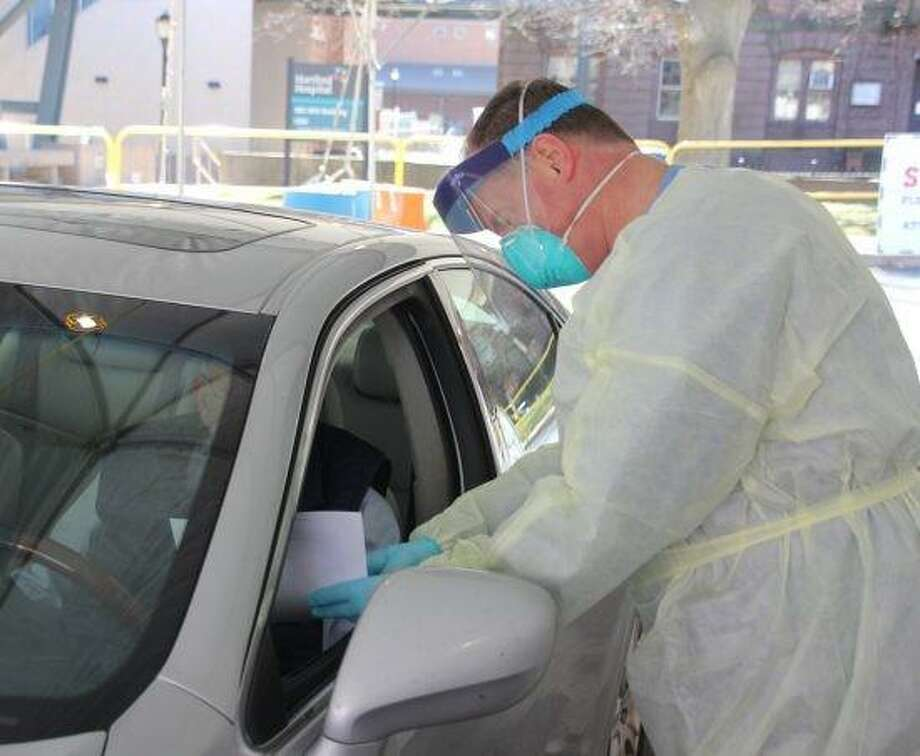 A medical practitioner meets a drive-through patient for coronavirus testing at Hartford Hospital Monday. Photo: Hartford HealthCare / Contributed Photo