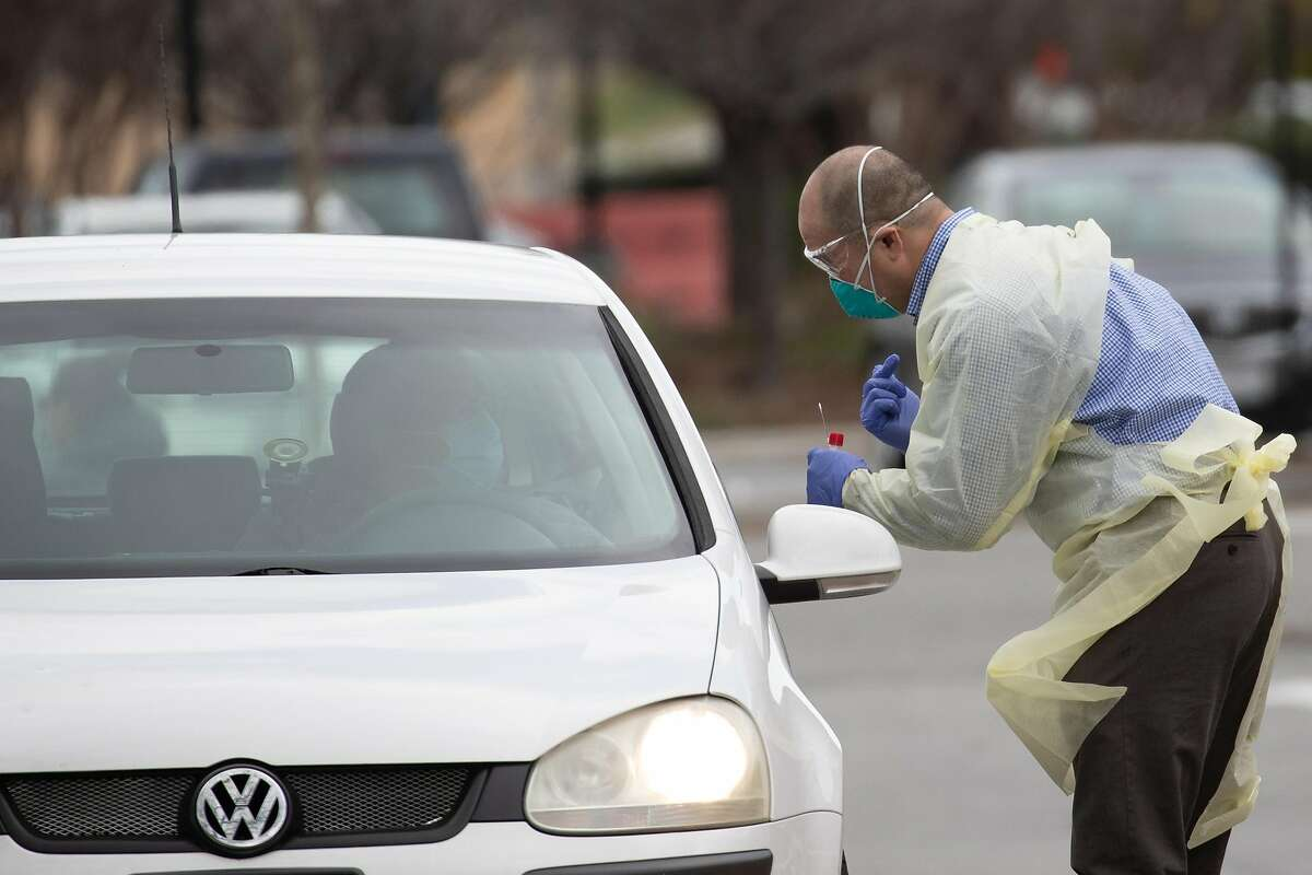 A medical professional prepares to take a saliva sample at a drive-through COVID-19 testing site at Kaiser Permanente - Redwood City Tuesday, March 17, 2020, in Redwood City, Calif.