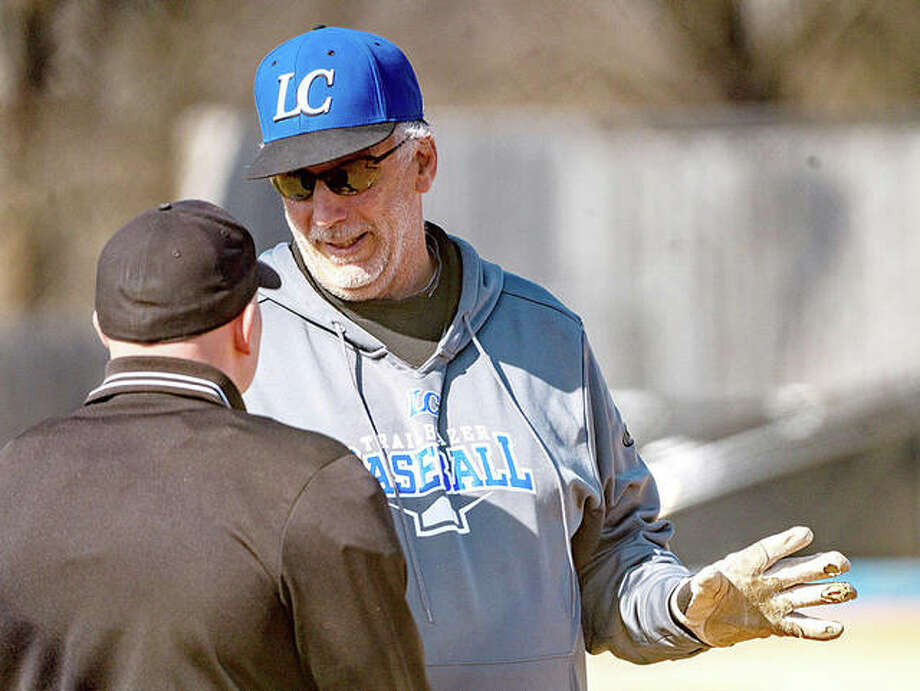 Lewis and Clark Community College baseball coach Randy Martz, rigyht, talks with an umpire during a game earlier this month in Godfrey against Kirkwood College. Photo: Nathan Woodside | The Telegraph