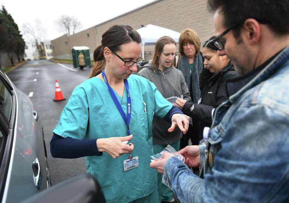 Nurses Michelle DiLorenzo, LPN, left, and Mark Pullo, RN, practice bagging a test sample in preparation for drive through coronavirus testing at St. Vincent's Bridgeport Health & Wellness Center at 2979 Main Street in Bridgeport, Conn. on Tuesday, March 17, 2020. Bridgeport Hospital began drive through testing, with a doctor's letter, on Tuesday. Photo: Brian A. Pounds / Hearst Connecticut Media / Connecticut Post