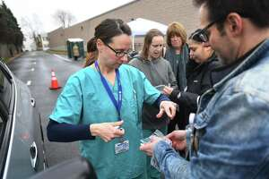 Nurses Michelle DiLorenzo, LPN, left, and Mark Pullo, RN, practice bagging a test sample in preparation for drive through coronavirus testing at St. Vincent's Bridgeport Health & Wellness Center at 2979 Main Street in Bridgeport, Conn. on Tuesday, March 17, 2020. Bridgeport Hospital began drive through testing, with a doctor's letter, on Tuesday.