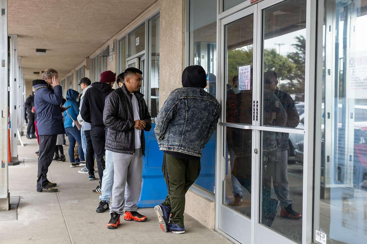 People wait in line to enter City Arms on Tuesday, March 17, 2020, in Pacifica, Calif.