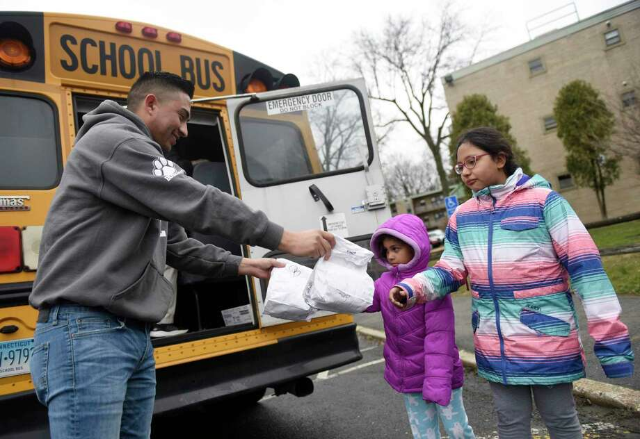 New Lebanon School special education teacher Johnny Quezada gives bagged lunches to first-grader Kori Chavoya and fourth-grader Haylli Chavoya at the Armstrong Court housing development in the Chickahominy section of Greenwich, Conn. Tuesday, March 17, 2020. The school district is providing breakfast and lunch Monday through Friday to more than 1,000 students who qualify for free and reduced lunches by sending buses to 12 locations throughout town for students and parents to pick up their meals. Photo: Tyler Sizemore / Hearst Connecticut Media / Greenwich Time