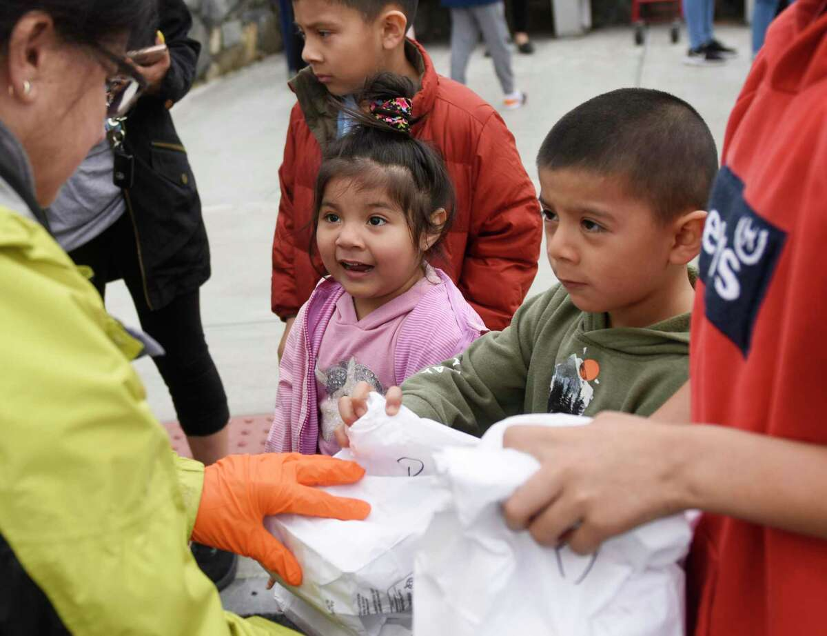 Ashley and Gustavo Ramirez take a bagged meal at New Lebanon School in the Byram section of Greenwich, Conn. Tuesday, March 17, 2020. The school district is providing breakfast and lunch Monday through Friday to more than 1,000 students who qualify for free and reduced lunches by sending buses to 12 locations throughout town for students and parents to pick up their meals.