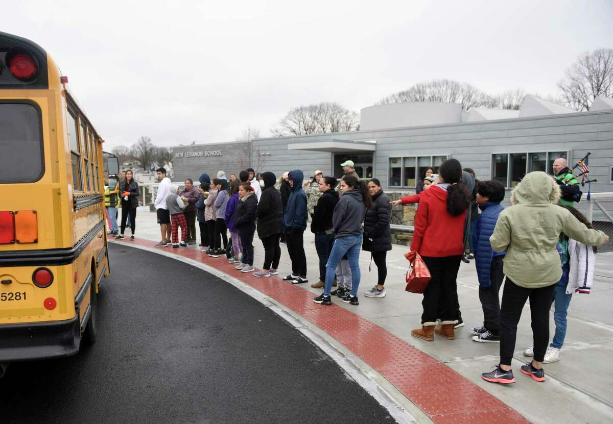 Students and parents line up to receive bagged lunches at New Lebanon School in the Byram section of Greenwich, Conn. Tuesday, March 17, 2020. The school district is providing breakfast and lunch Monday through Friday to more than 1,000 students while schools are closed.