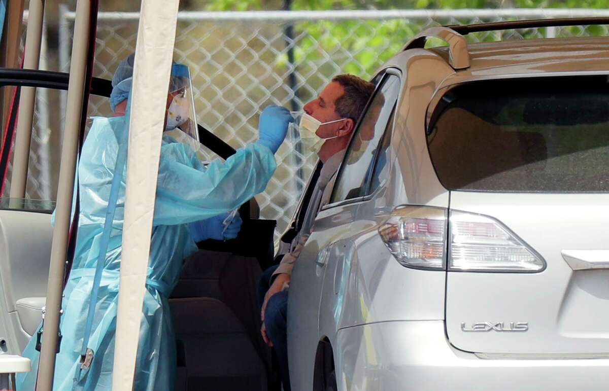 A medical worker tests a person for the coronavirus at a drive-through facility primarily for first responders and medical personnel in San Antonio on Tuesday, March 17, 2020.