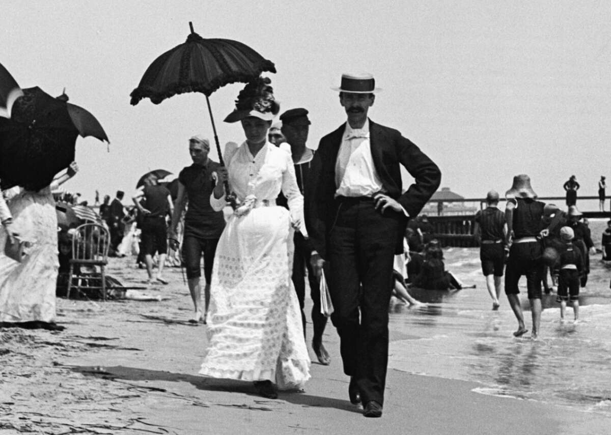 """1890: Couple walks along the beach in Atlantic City Seaside socializing rose to popularity in the 19th century, beginning in Britain where doctors were encouraging beach visits as a way to combat """"melancholy,"""" and later in America as the trend hit the East Coast. The first boardwalk stateside was built in Atlantic City in 1870 by two men-a hotelier and a railroad conductor-who had grown aggravated with beachgoers consistently dragging sand into their resorts and train cars. It was very basic, consisting only of an arrangement of boards laid out on the sand, and was later replaced by a larger railed boardwalk in 1890. In this photo, people stroll along the sand at the New Jersey beach, with the boardwalk in the background."""