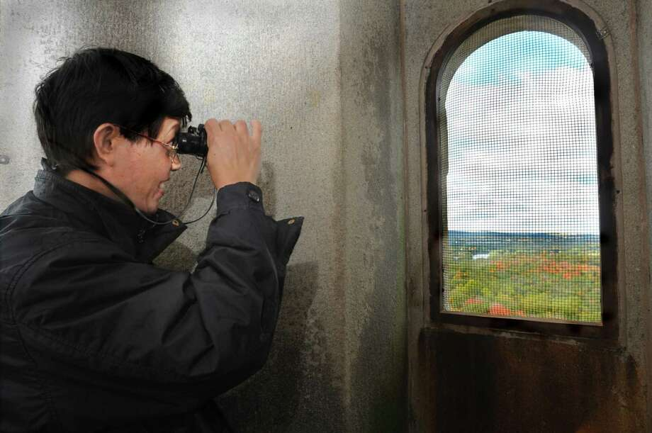 (ms101610)-Winston Zhang, of New Haven, looks out at Sleeping Giant State Park from the top of the Soldiers' and Sailors' Monument at East Rock Park. Melanie Stengel/Register