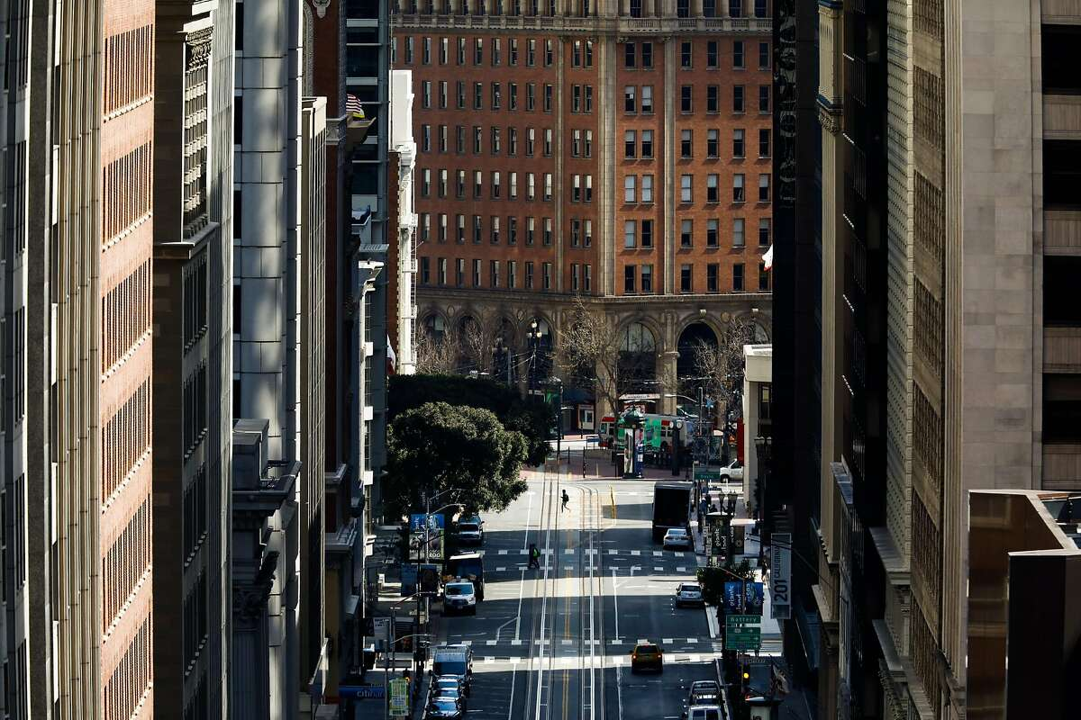 A pedestrian walks through the financial district on Tuesday, March 17, 2020 in San Francisco, California. The city is on lockdown due to the coronavirus.