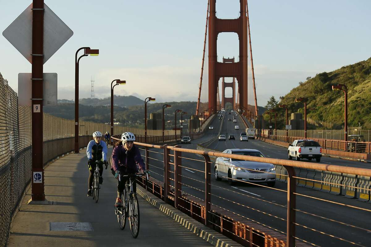 A pair of women bicycle across the Golden Gate Bridge Tuesday, March 17, 2020, in Sausalito, Calif. About 7 million people in the San Francisco Bay Area woke up Tuesday to nearly empty highways, shuttered stores and vacant streets after officials issued an order for residents to shelter at their homes and only leave for