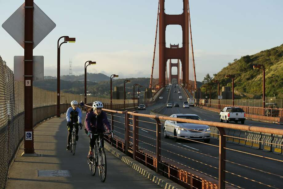 """A pair of women bicycle across the Golden Gate Bridge Tuesday, March 17, 2020, in Sausalito, Calif. About 7 million people in the San Francisco Bay Area woke up Tuesday to nearly empty highways, shuttered stores and vacant streets after officials issued an order for residents to shelter at their homes and only leave for """"essential"""" reasons in a desperate attempt to slow the spread of the coronavirus. (AP Photo/Eric Risberg) Photo: Eric Risberg, Associated Press"""