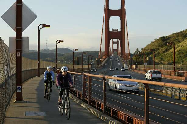 """A pair of women bicycle across the Golden Gate Bridge Tuesday, March 17, 2020, in Sausalito, Calif. About 7 million people in the San Francisco Bay Area woke up Tuesday to nearly empty highways, shuttered stores and vacant streets after officials issued an order for residents to shelter at their homes and only leave for """"essential"""" reasons in a desperate attempt to slow the spread of the coronavirus. (AP Photo/Eric Risberg)"""