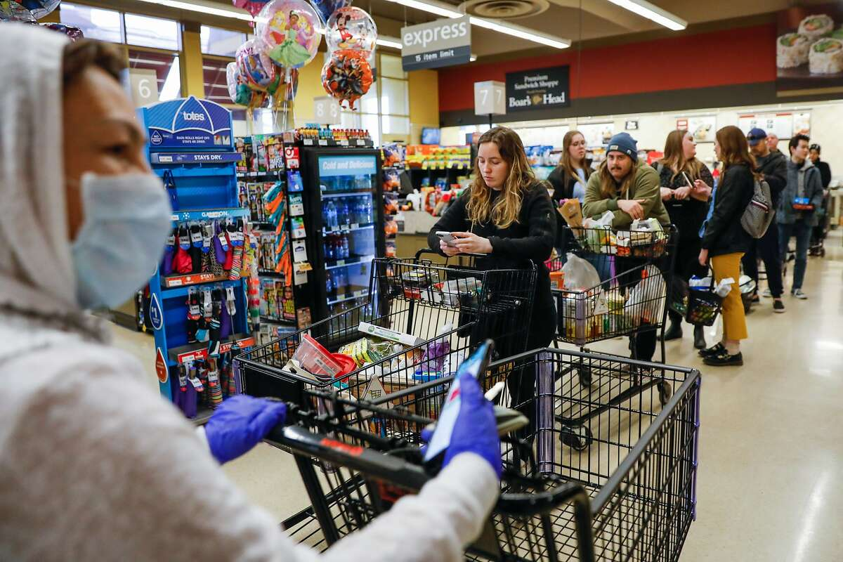 Cassidy Butler (center) and others wait on line at Safeway on 7th Avenue on Tuesday, March 17, 2020 in San Francisco, California. The city is on lockdown due to the coronavirus.