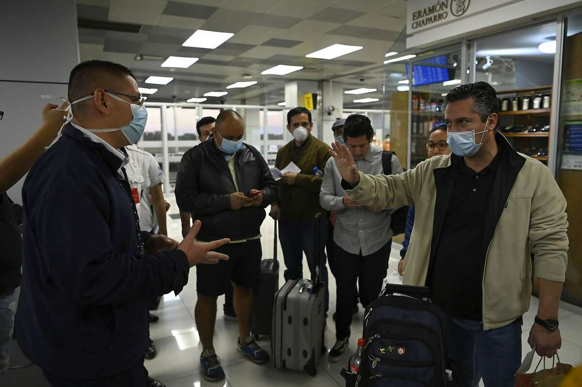 Passengers who were refused entry to El Salvador before they complete a quarantine, talk to an official (L) wearing a face mask as a precaution against the spread of the new coronavirus, COVID-19, at San Oscar Romero International Airport in San Luis Talpa, El Salvador, on March 12, 2020. - El Salvador banned entry to all foreigners for a period of 21 days in a bid to curb the spread of the coronavirus, the Central American country's president announced on March 11. Salvadorans arriving from countries where coronavirus has been declared would have to be quarantined for 30 days. (Photo by Marvin RECINOS / AFP) (Photo by MARVIN RECINOS/AFP via Getty Images)