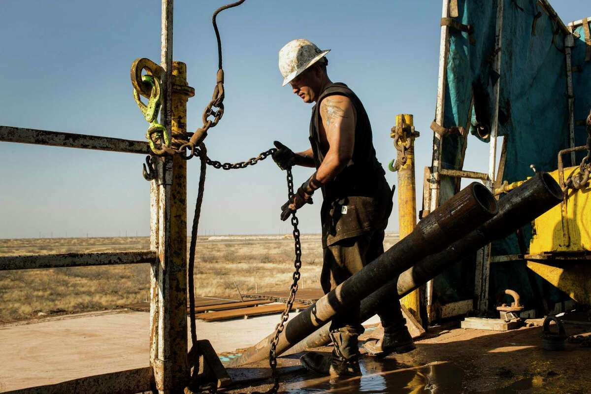 A worker prepares to lift drills by pulley to the main floor of Endeavor Energy Resources LP's Big Dog Drilling Rig 22 in the Permian basin outside of Midland, Texas. The most prolific shale drillers in Texas have cut at least $7.6 billion from their combined 2020 capital expenditures budgets while several more are expected to follow suit as crude oil prices fall to lowest levels since the bottom of the last oil bust, which was considered worst in a generation.