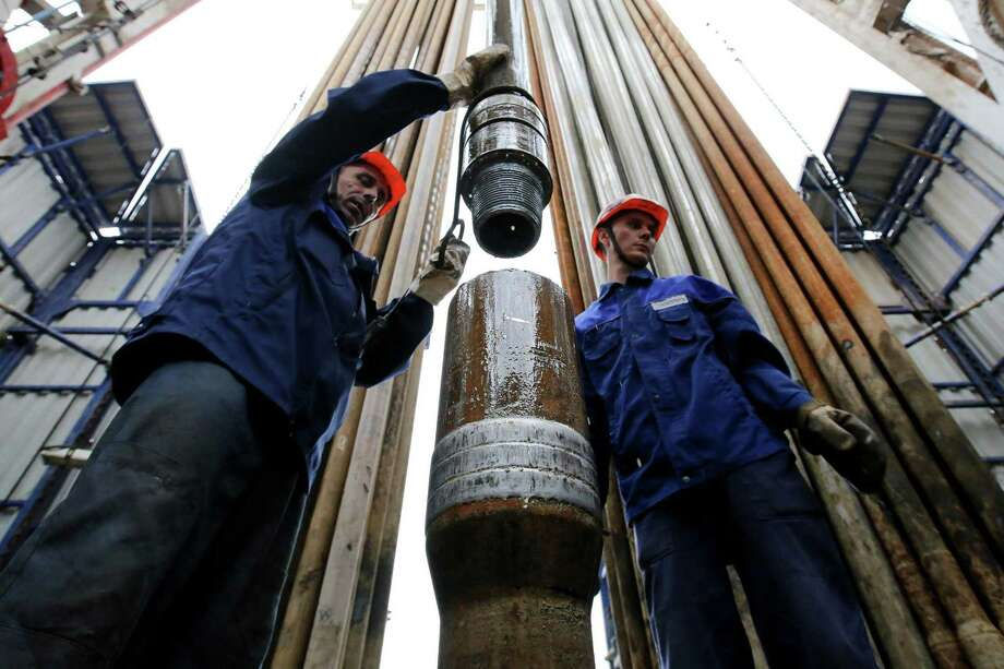 Workers secure drilling pipe sections on an oil drilling tower operated by Tatneft near Almetyevsk, Russia. Crude oil prices are near four-year lows and are only expected to fall further as a price war between Russia and Saudi Arabia floods global markets with even more crude oil even as demand for crude oil, jet fuel, gasoline and diesel shrinks around the world. Photo: Andrey Rudakov / Bloomberg / © 2015 Bloomberg Finance LP