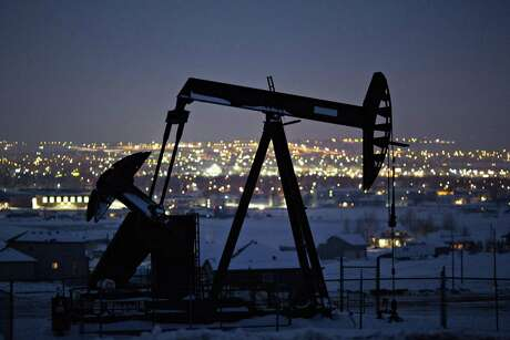 A pumpjack operates above an oil well at night in the Bakken Formation on the outskirts of Williston, North Dakota. The most prolific shale drillers in Texas have cut at least $7.6 billion from their combined 2020 capital expenditures budgets while several more are expected to follow suit as crude oil prices fall to lowest levels since the bottom of the last oil bust, which was considered worst in a generation.