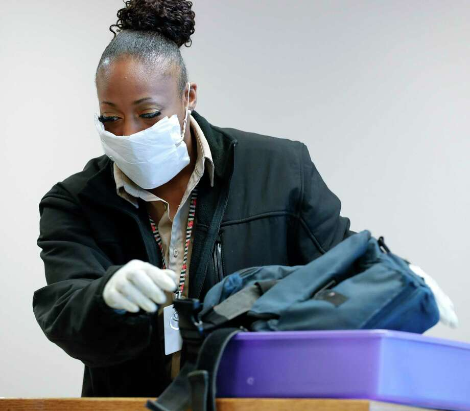 Security worker Shawna Butler handles visitors' personal effects wearing a makeshift mask made from a napkin and a rubber band before a Montgomery County Commissioners Court meeting at the Alan B. Sadler Commissioners Court Building, Tuesday, March 17, 2020, in Conroe. Photo: Jason Fochtman, Houston Chronicle / Staff Photographer / Houston Chronicle  © 2020