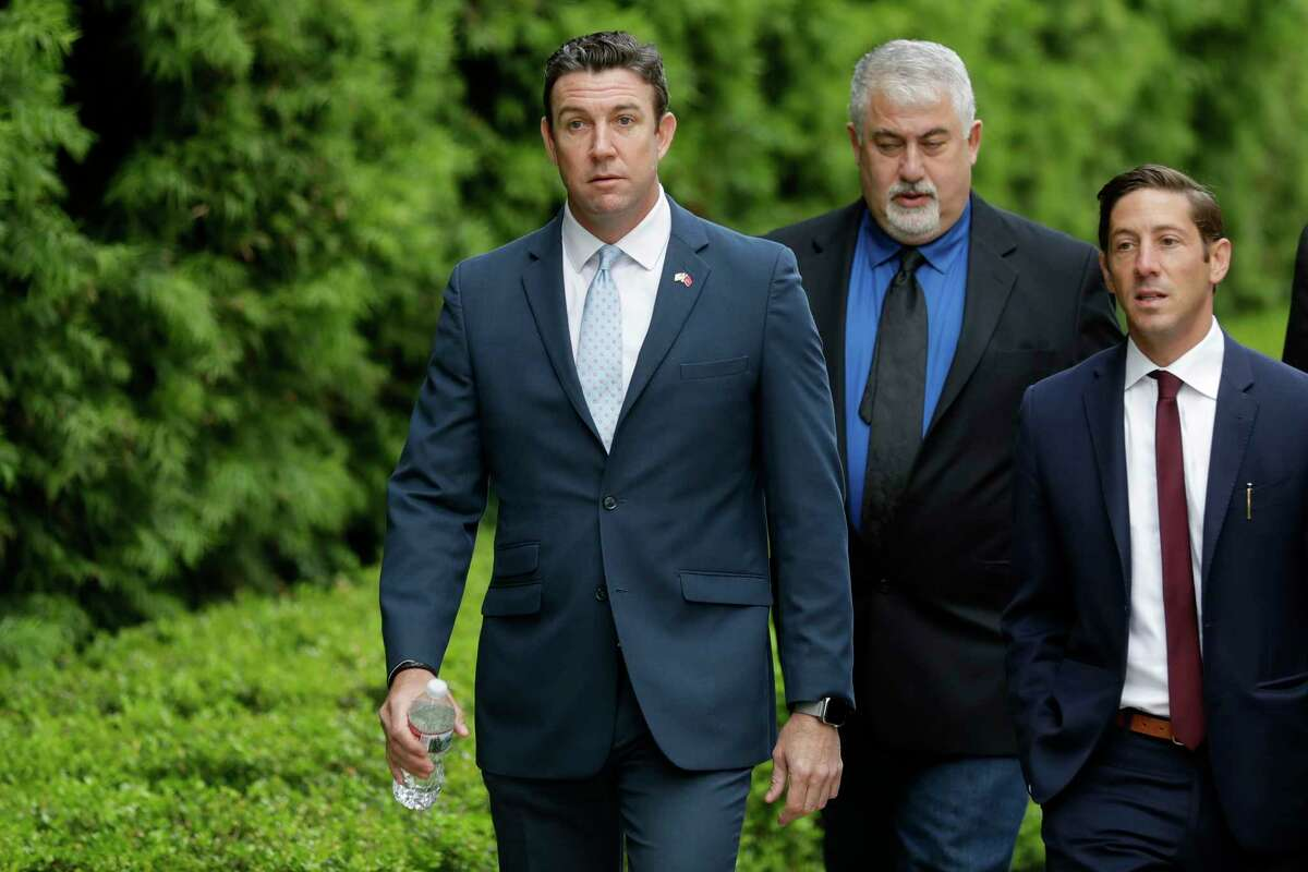Convicted ex-Rep. Duncan Hunter, left, walks towards a court building for sentencing Tuesday, March 17, 2020, in San Diego. Hunter faces up to five years in prison after pleading guilty on a corruption charge. Hunter served six terms representing one of Southern California's last solidly Republican districts before he resigned.A (AP Photo/Gregory Bull)