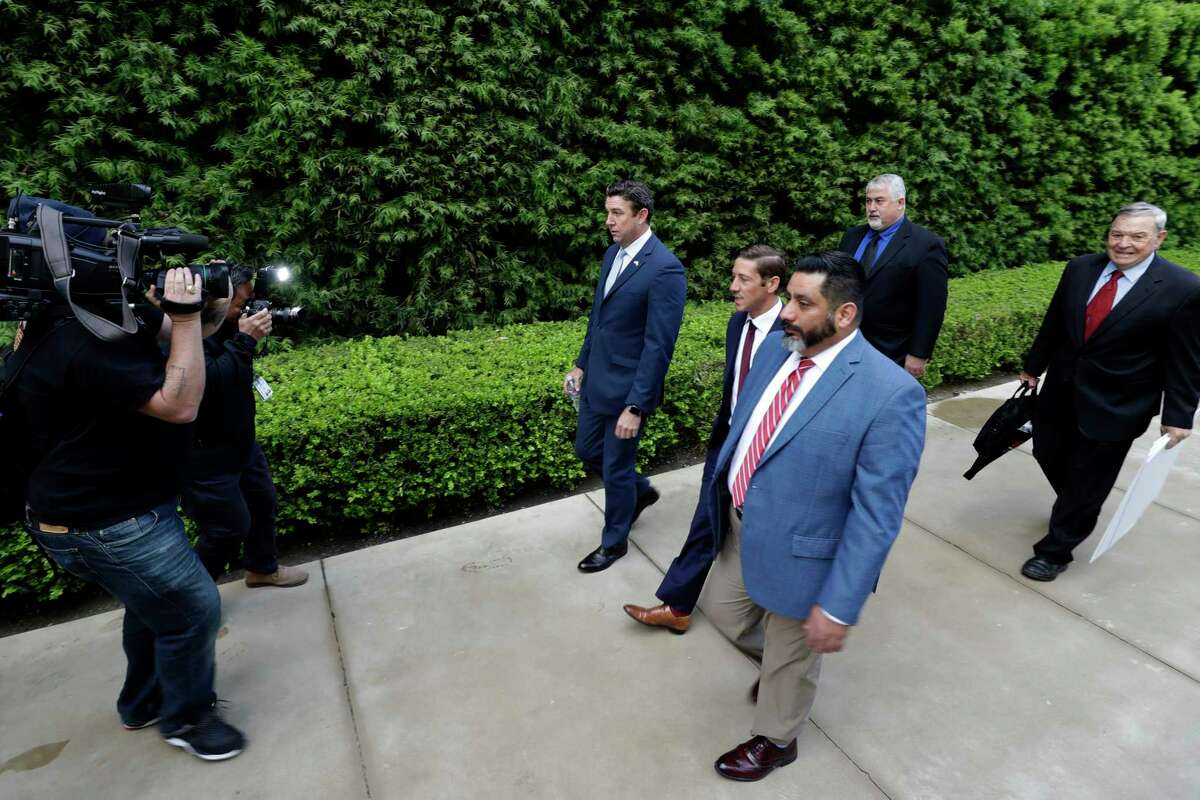 Convicted ex-Rep. Duncan Hunter, center left, walks towards a court building for sentencing Tuesday, March 17, 2020, in San Diego. Hunter faces up to five years in prison after pleading guilty on a corruption charge. (AP Photo/Gregory Bull)