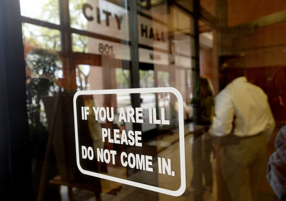 A sign posted outside the chambers asks those who are sick not to attend Tuesday's City Council meeting, and an overflow room was in place to keep the number of those in attendance below 50. Photo taken Tuesday, March 17, 2020 Kim Brent/The Enterprise Photo: Kim Brent/The Enterprise
