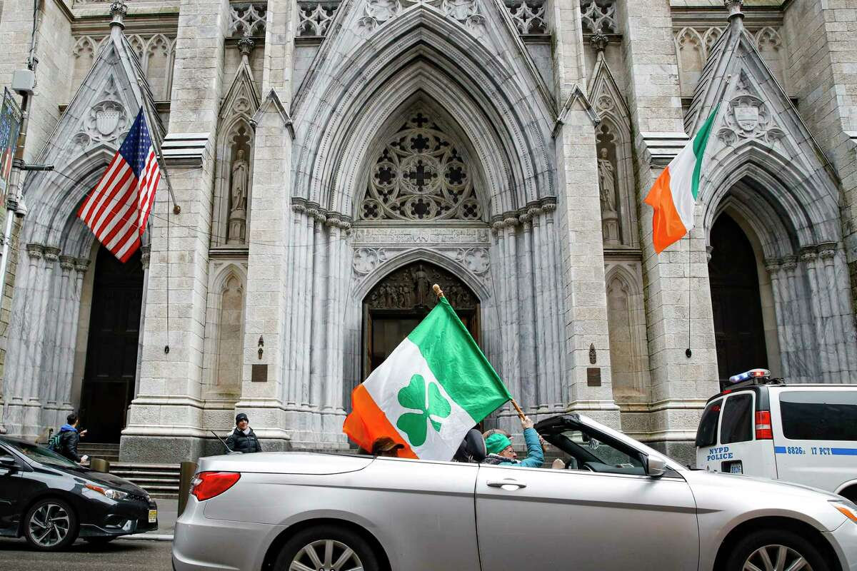 A woman holding an Irish themed flag is driven by St. Patrick's Cathedral after the annual parade was cancelled due to coronavirus concerns, Tuesday, March 17, 2020, in New York. New York state entered a new phase in the coronavirus pandemic Monday, as New York City closed its public schools, and officials said schools statewide would close by Wednesday. New York joined with Connecticut and New Jersey to close bars, restaurants and movie theaters along with setting limits on social gatherings. (AP Photo/John Minchillo)