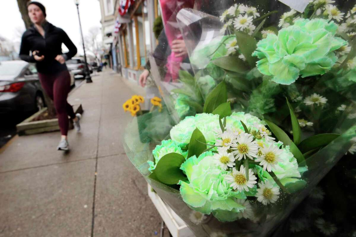 A woman runs past a bouquet of green carnations and daisies outside a floristshop on a nearly empty sidewalk on Broadway on St. Patrick's Day in the South Boston neighborhood of Boston, Tuesday, March 17, 2020. For most people, the new coronavirus causes only mild or moderate symptoms. For some, it can cause more severe illness, especially in older adults and people with existing health problems. (AP Photo/Charles Krupa)