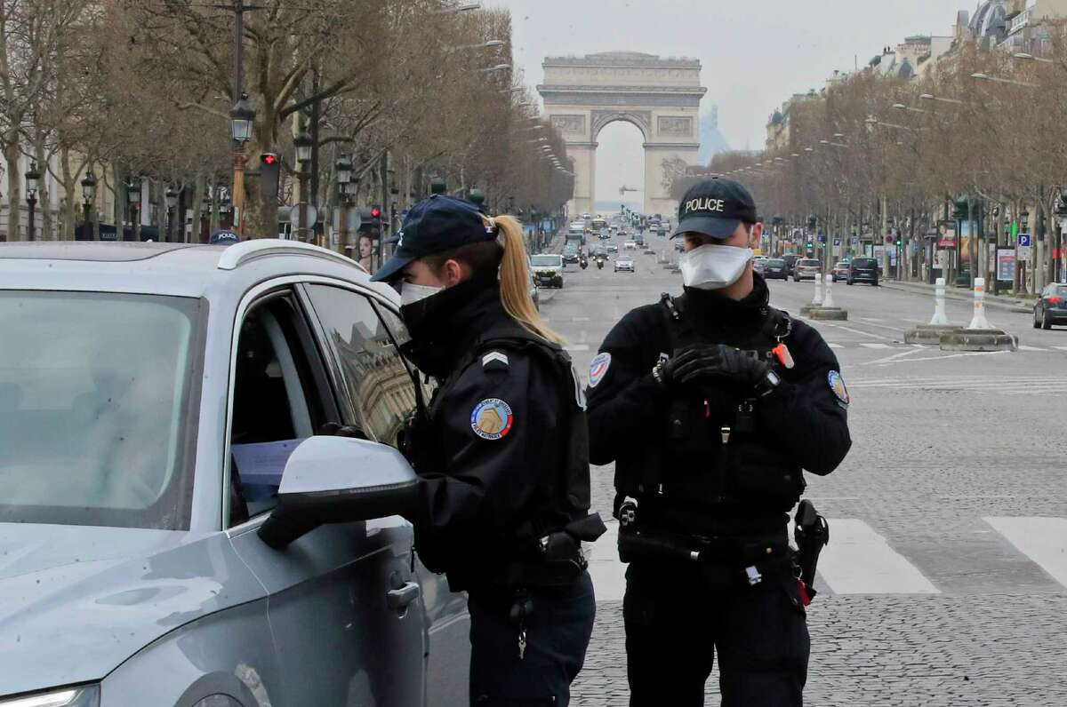 Police officers wearing protective masks check papers at a control point at the Champs Elysees avenue in Paris, Tuesday, March 17, 2020. France is imposing nationwide restrictions on how far from their homes people can go and for what purpose as part of the country's strategy to stop the spread of the new coronavirus. For most people, the new coronavirus causes only mild or moderate symptoms, such as fever and cough. For some, especially older adults and people with existing health problems, it can cause more severe illness, including pneumonia. (AP Photo/Michel Euler)