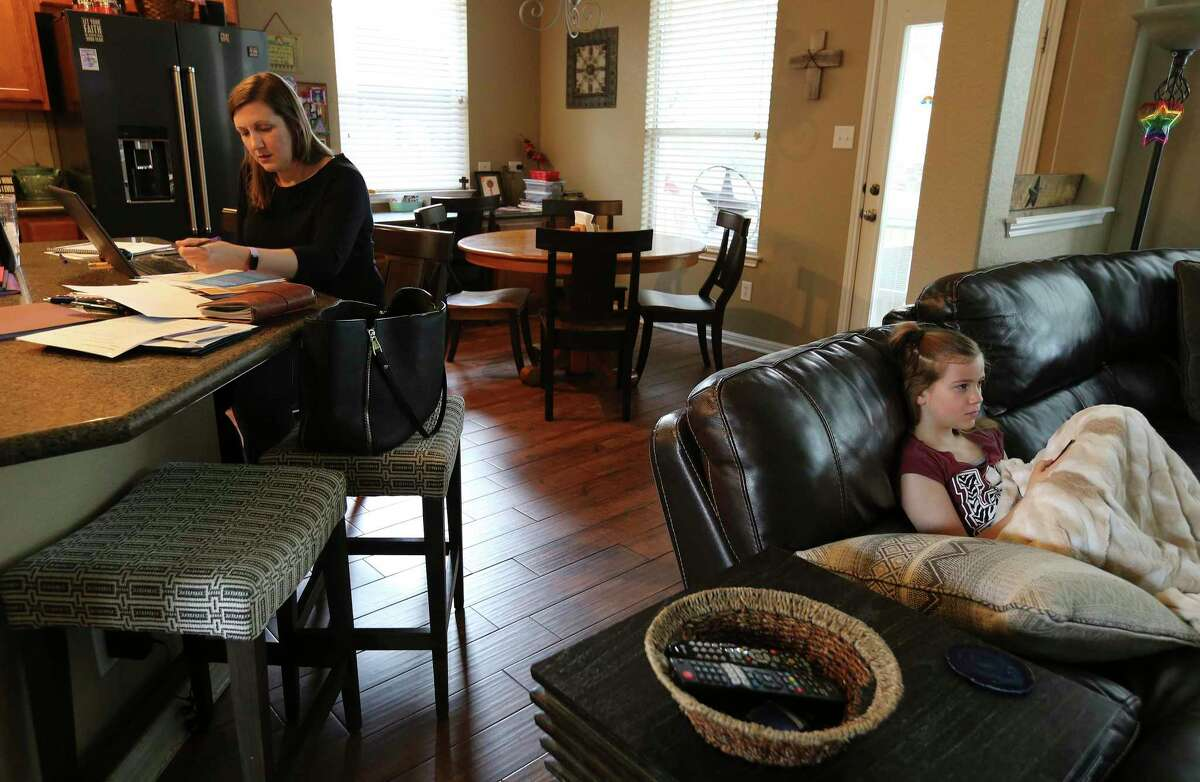 Ashley Schneider tends to her work as a marketing manager for Jefferson Bank while her 9-year-old daughter, Lauren, watches a show Tuesday, Mar. 17, 2020.