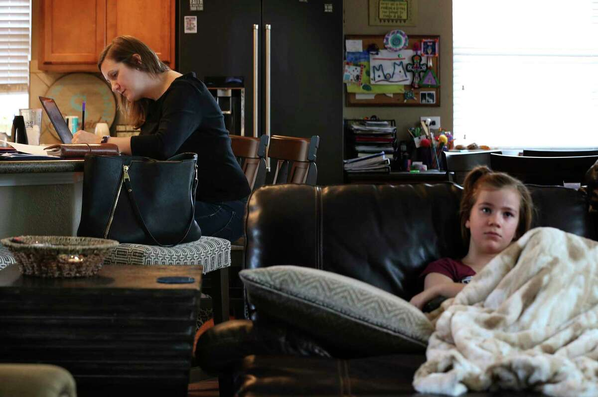 Ashley Schneider is working from home and watching her children while they're out of school. Lauren, 9, watches TV Tuesday, March 17, 2020.