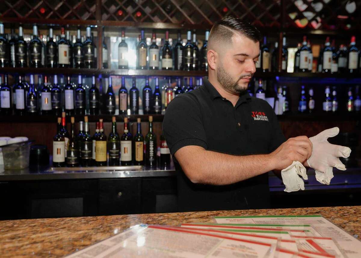 Fidan Haliti puts on gloves as he prepares to help sanitizes the bar at Joe's Pizza & Pasta after Montgomery County Judge Mark Keough issued restrictions for restaurants and bars, Tuesday, March 17, 2020, in Conroe. Under the new guidelines, restaurants and bars are to reduce occupancy of the establishments to no more than 50 people, and tables are to be spaced a minimum of 10 feet apart. Establishments are still allowed to offer to-go and catering options, as well as delivery.