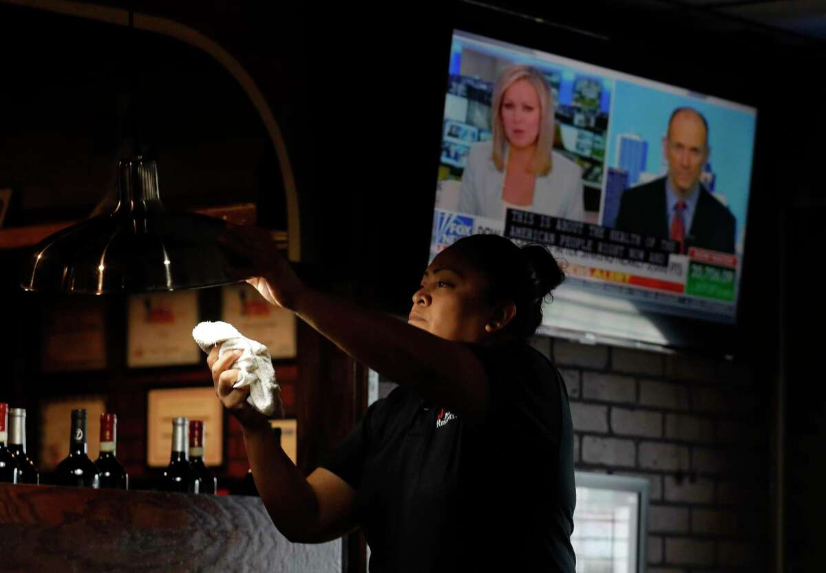 Brenda Galicia sanitizes lights and tables as a news cast discusses the latest news on conrovirus at Joe's Pizza & Pasta after Montgomery County Judge Mark Keough issued restrictions for restaurants and bars, Tuesday, March 17, 2020, in Conroe. Under the new guidelines, restaurants and bars are to reduce occupancy of the establishments to no more than 50 people, and tables are to be spaced a minimum of 10 feet apart. Establishments are still allowed to offer to-go and catering options, as well as delivery.