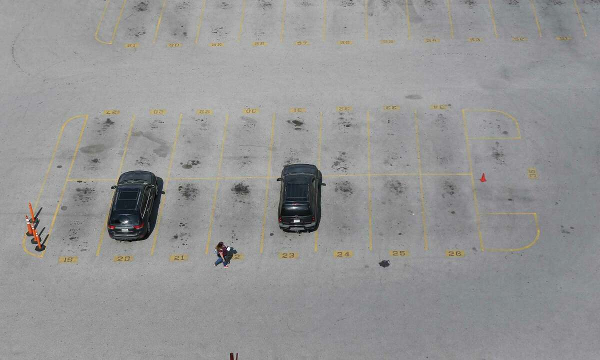 A woman walks to one of two parked cars in an otherwise completely empty parking lot at Franklin and La Branch Streets Tuesday, March 17, 2020, in Houston. The city is seeing less traffic because of the Coronavirus (COVID-19) outbreak.