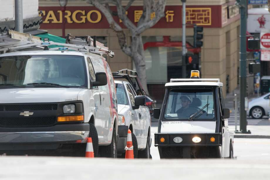 A meter maid checks parking meters. San Francisco had its first shelter-in-place day on March 17th, 2020 in response to the spread of the COVID-19 coronavirus. Photo: Douglas Zimmerman/SFGate