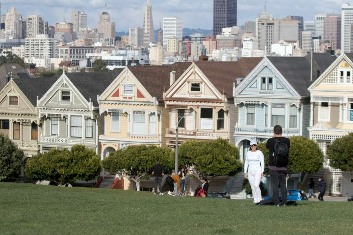 A couple poses for a photo in front of the Painted Ladies at Alamo Square.