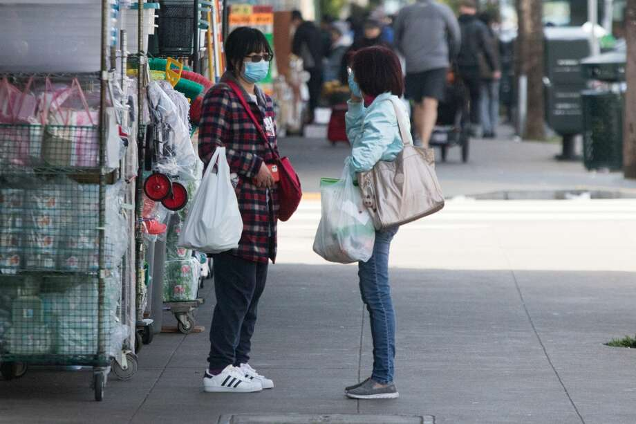 Took woman wearing masks talk on Irving Street. San Francisco had its first shelter-in-place day on March 17th, 2020 in response to the spread of the COVID-19 coronavirus. Photo: Douglas Zimmerman/SFGate